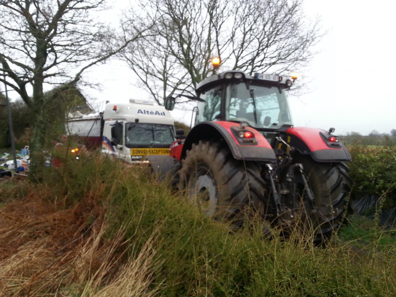 Un tracteur tire le convoi enlisé dans la boue