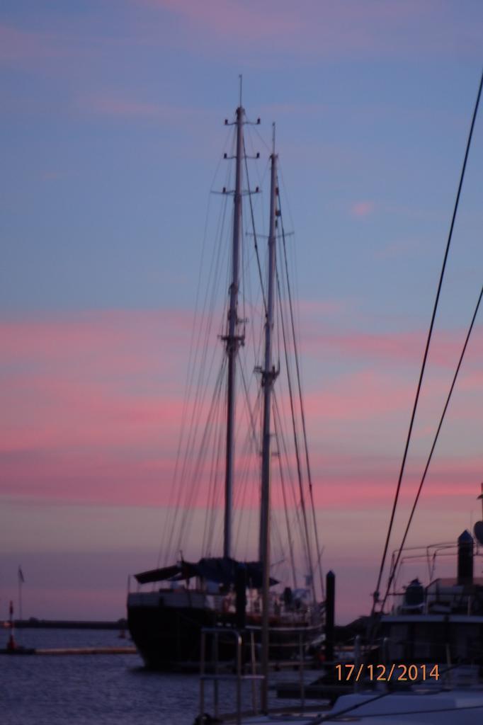 un voilier au coucher de soleil dans la marina