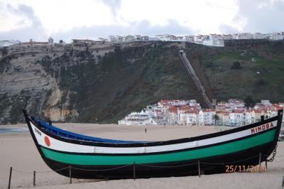 La plage de Nazaré et un bateau de pêche survivant